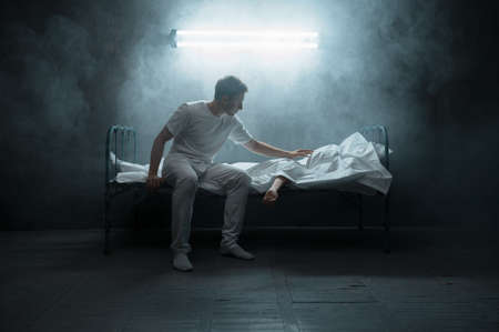 Sad psycho man looking on dead woman in bed
