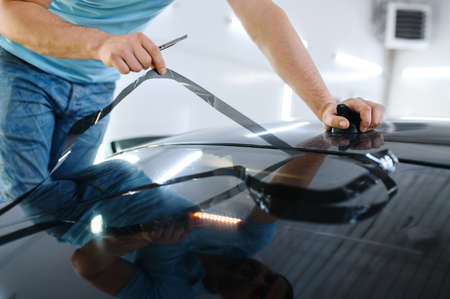 Male wrapper cuts car tinting, tuning service Imagens