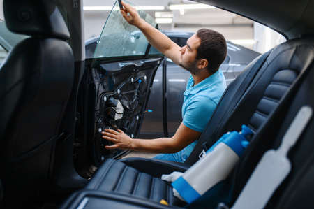Worker prepares car for tinting, tuning service