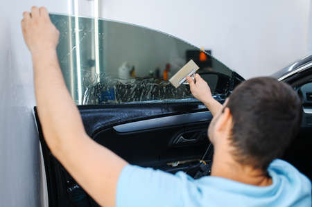 Male worker with squeegee installs car tinting Reklamní fotografie