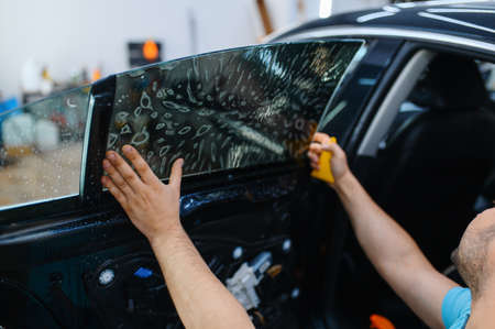 Worker installs wetted car tinting, tuning service