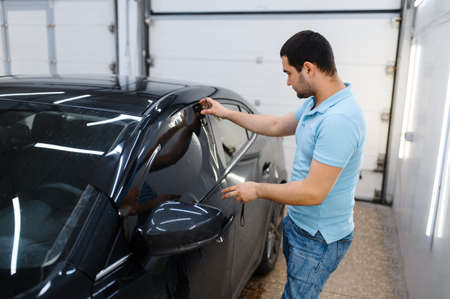 Male worker tries on wetted car tinting, tuning