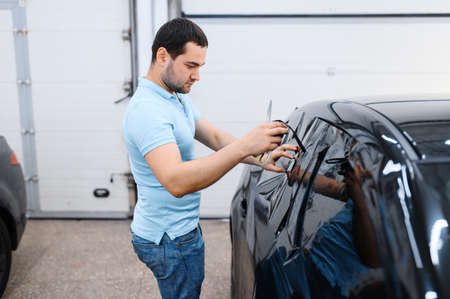 Worker holds film, car tinting installation