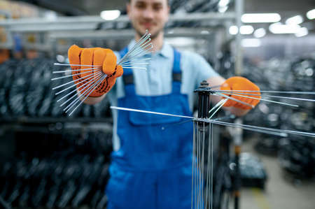Worker shows new bicycle spokes on factory Banque d'images