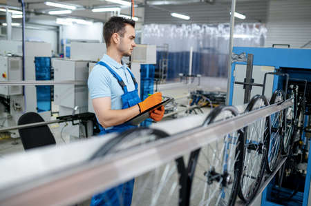 Worker at the machine tool makes bicycle rim