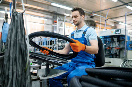 Worker at the assemly line holds bicycle tire