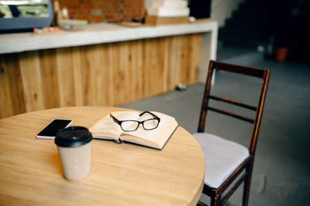 Book, coffee and glasses on table in student cafe
