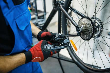Bicycle repair workshop, man sets the speed switc