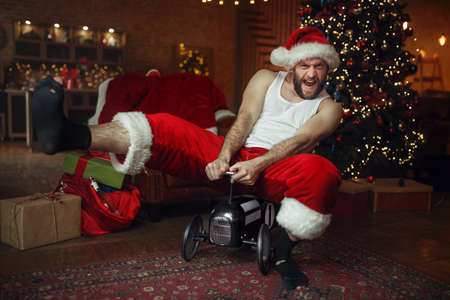 Bad drunk Santa claus riding on little toy car
