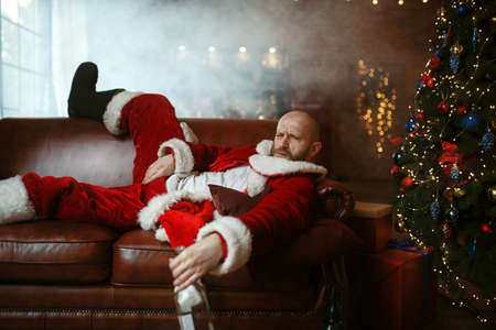 Bad drunk Santa claus lying on sofa after party