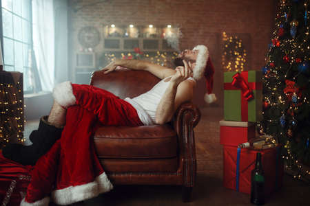 Vile Santa claus in red cap smoking cigar on couch