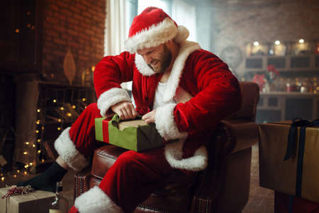 Bad drunk Santa claus opens gifts, humor Stock Photo