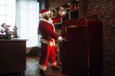 Bad Santa claus steals alcohol from refrigerator
