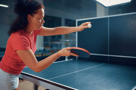 Woman hits ball at the wall, table tennis training