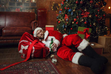 Bad drunk Santa claus sleeps under christmas tree