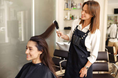 Hairdresser works with comb, hairdressing salon