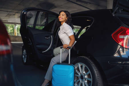 Woman with suitcase gets into the car on parking