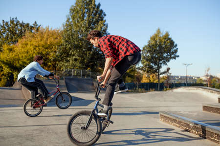 Two male bmx bikers doing tricks in skatepark 스톡 콘텐츠