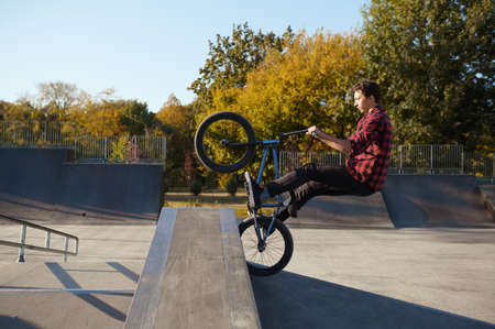 Young male bmx biker jumps on the wall 스톡 콘텐츠