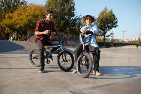 Two bmx bikers poses on ramp in skatepark