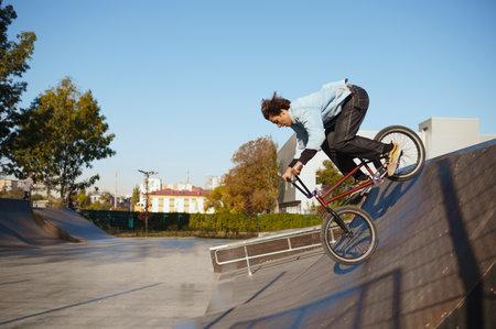 Bmx biker doing trick on ramp in skatepark 스톡 콘텐츠