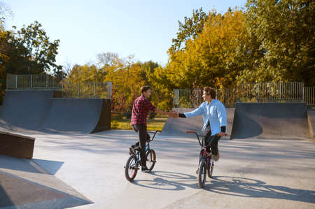 Two bmx bikers, training on ramp in skatepark