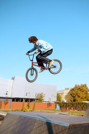 Male bmx biker doing trick on ramp in skatepark 스톡 콘텐츠