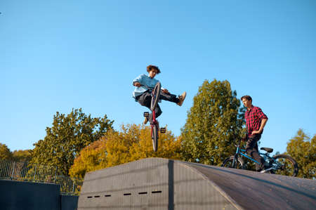 Bmx bikers jumps on ramp, training in skatepark