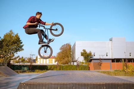 Male bmx biker jumps on ramp in skatepark