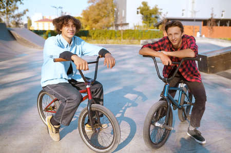 Bmx riders on bikes, training on ramp in skatepark 스톡 콘텐츠