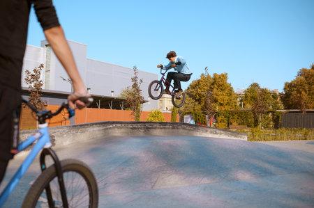 Bmx rider, jump in action, training in skatepark