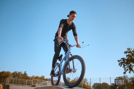 Male bmx biker, jump in action, skatepark 스톡 콘텐츠