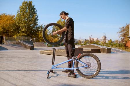 Young male bmx biker adjusts his bike in skatepark 스톡 콘텐츠