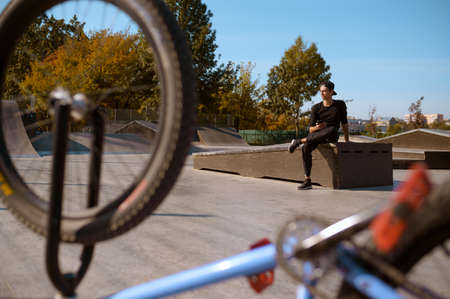 Male bmx rider poses in skatepark at the bike