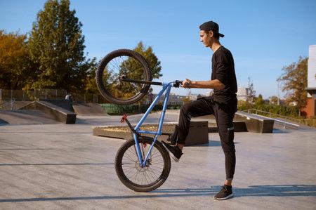 Male bmx biker doing trick, training in skatepark