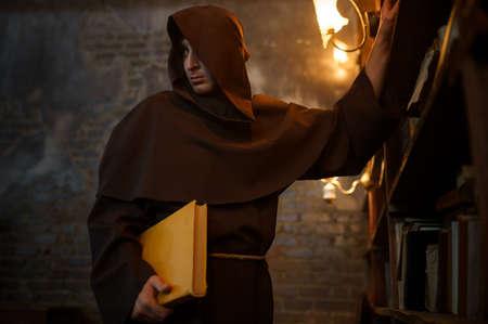 Male exorcist in black hood holding a torch Foto de archivo