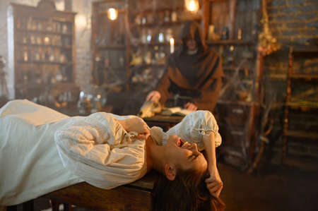 Exorcist casting out demons from crazy woman Foto de archivo