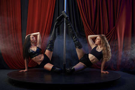 Two showgirls, pole dance, striptease dancers Stock Photo