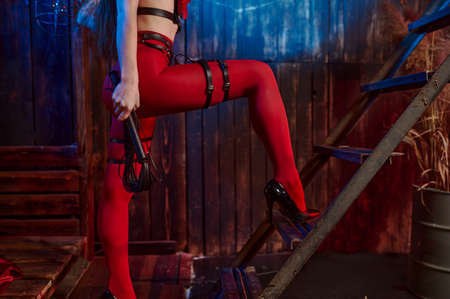 Sexy woman in red lingerie holds leather whip