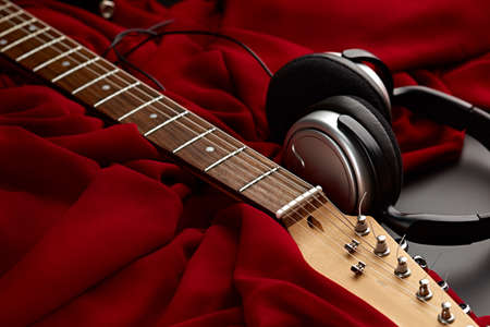 Electric guitar and headphones on red background