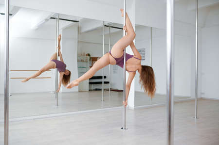 Sexy woman practice pole dance, workout in class Stock Photo