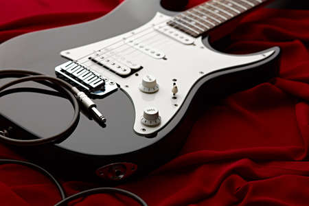 Black electric guitar, red background, nobody
