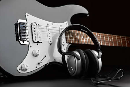 Electric guitar and headphones on black background