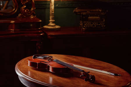 Violin in retro style on wooden table, closeup