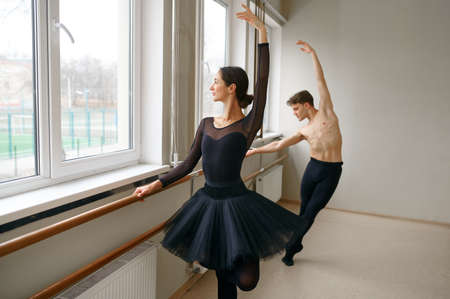 Female and male ballet dancers, exercise at barre