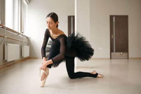 Ballerina doing stretching exercise in class