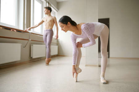 Couple of ballet dancers, stretching exercises
