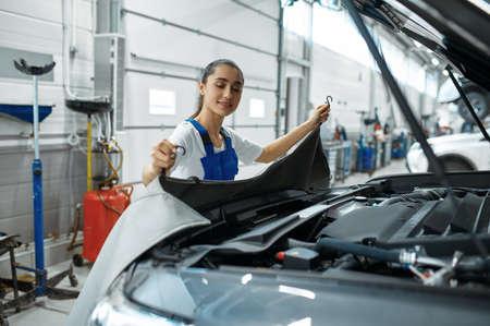 Female mechanic stands at the hood, car service Zdjęcie Seryjne