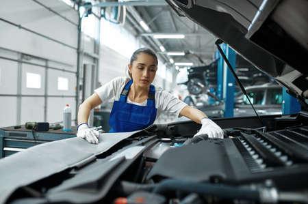 Female mechanic checks engine, car service Zdjęcie Seryjne