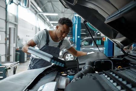 Male worker changes oil in engine, car service Zdjęcie Seryjne